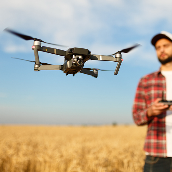 Man flying drone in agricultural field